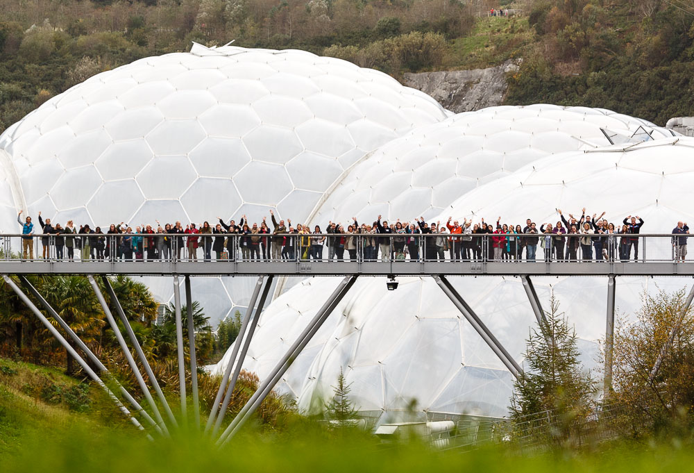 A large group of people at a Community Camp stand along a bridge waving with the Eden Project behind them