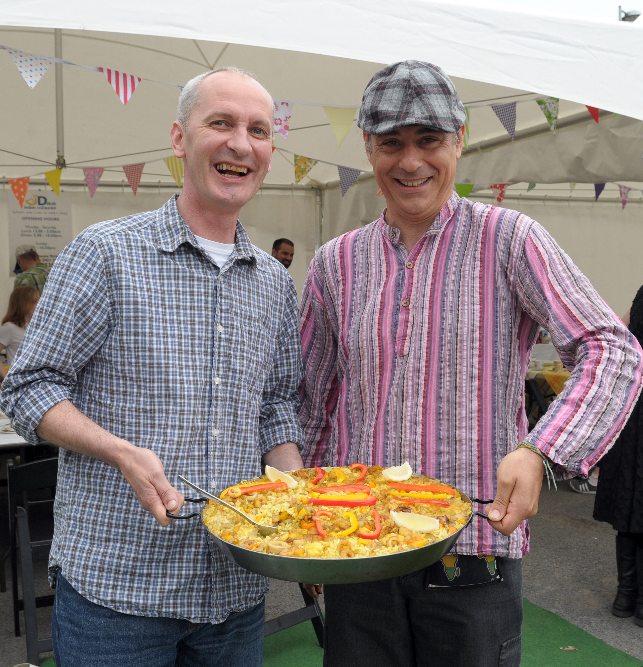 Two men holding up a giant paella.