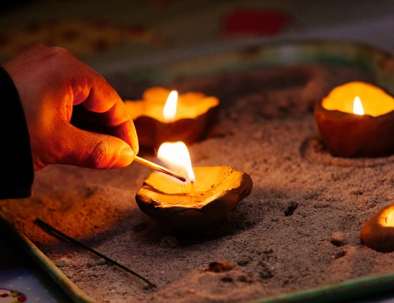 A hand lighting a tea light.