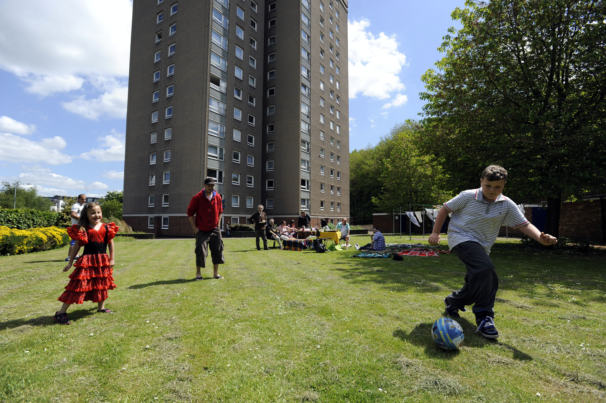 A group playing football and having lunch in a communal field between apartments.