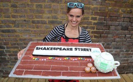 Hannah with a giant cake made to look like the Shakespeare Street sign.