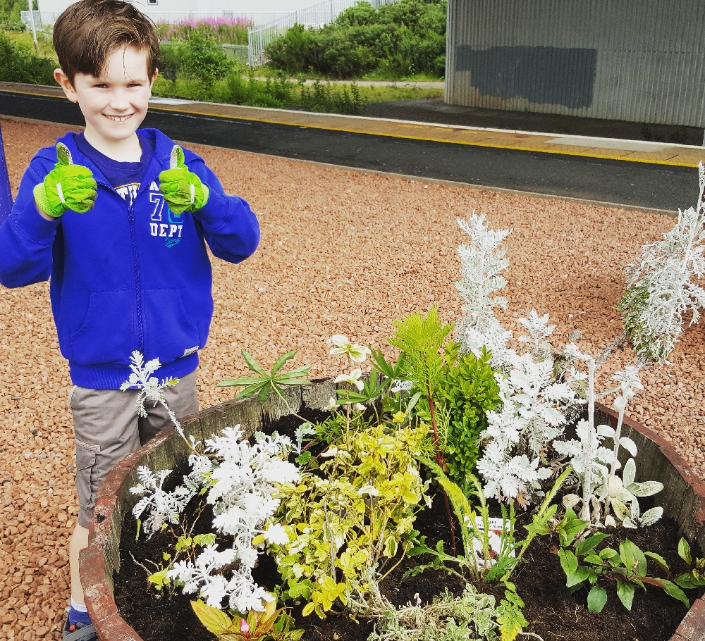 A boy giving the thumbs up to flowers he's just planted at a train station.