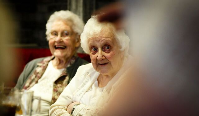 Two elderly women smiling.