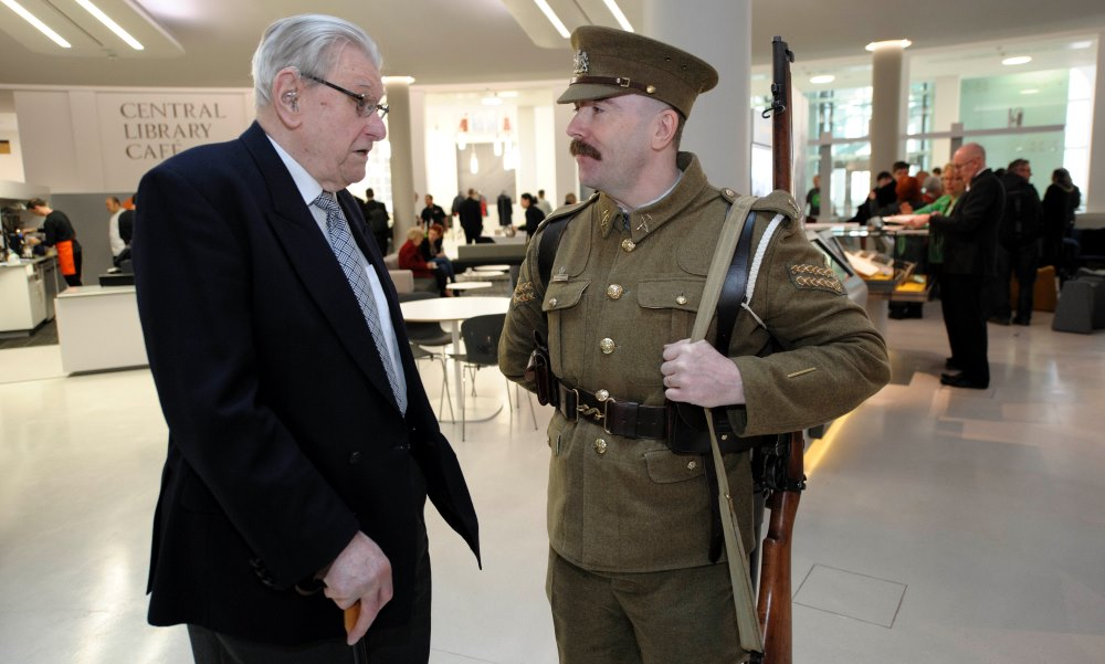 Two men talking, one is wearing a military uniform.