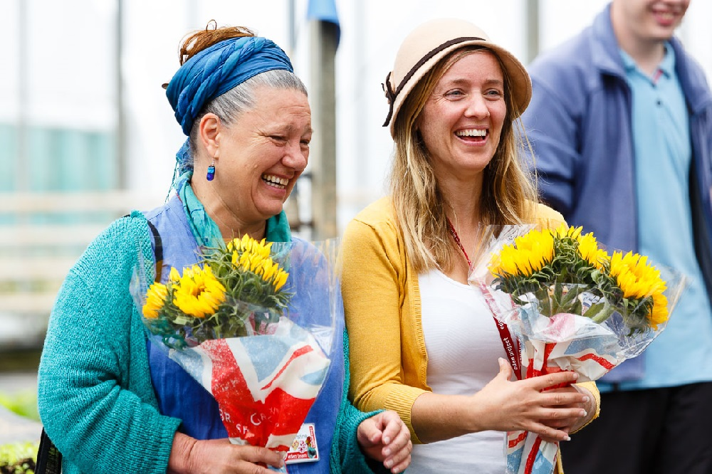 Two women laughing with a bunch of yellow flowers each.