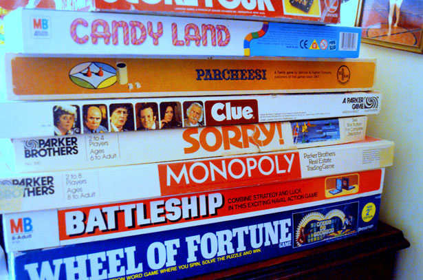 A stack of different board games including Monopoly and Battleships.
