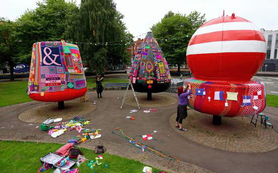 Large buoys covered in knitted slogans.