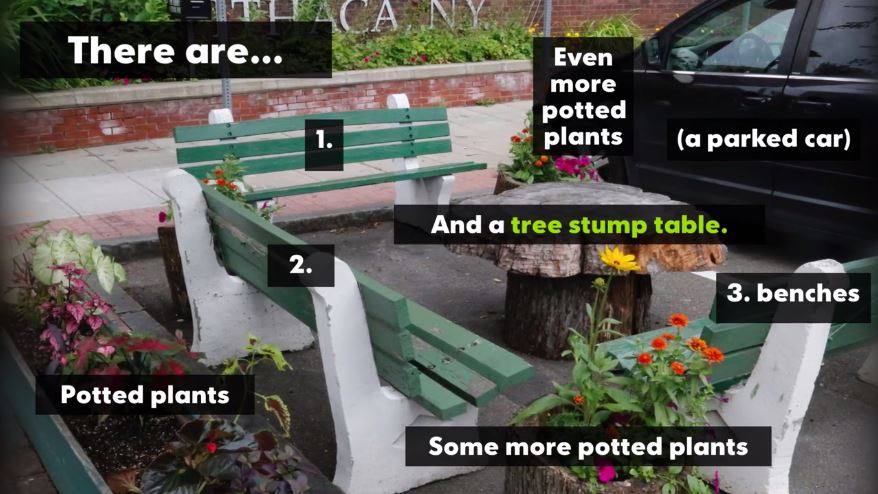 Car park space turned into a park. Three bench seats around the edges, a tree stump table in the centre and potted plants beside the bench seats.