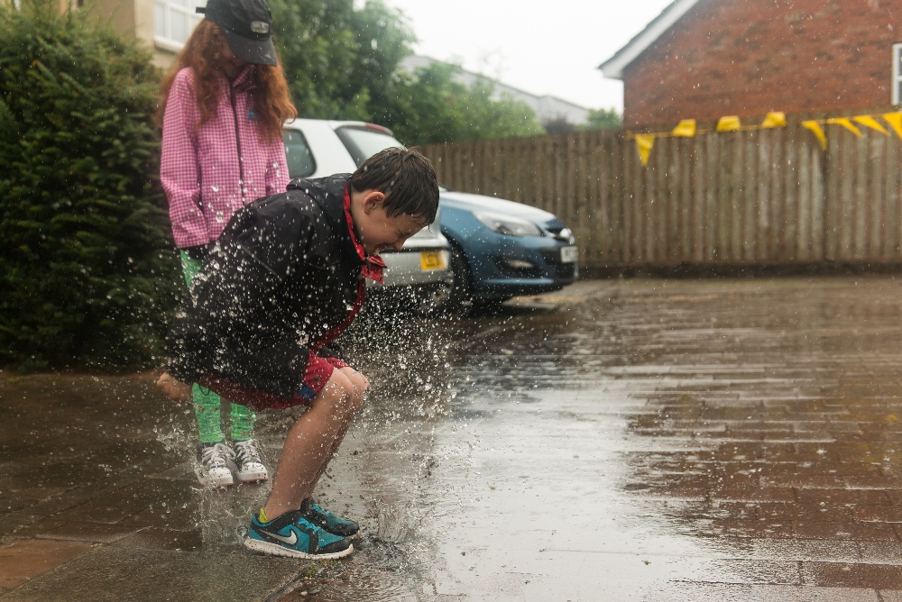 A boy jumping in a puddle.