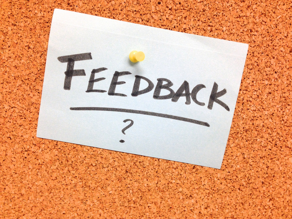 The word feedback written on a white note pinned to a board.