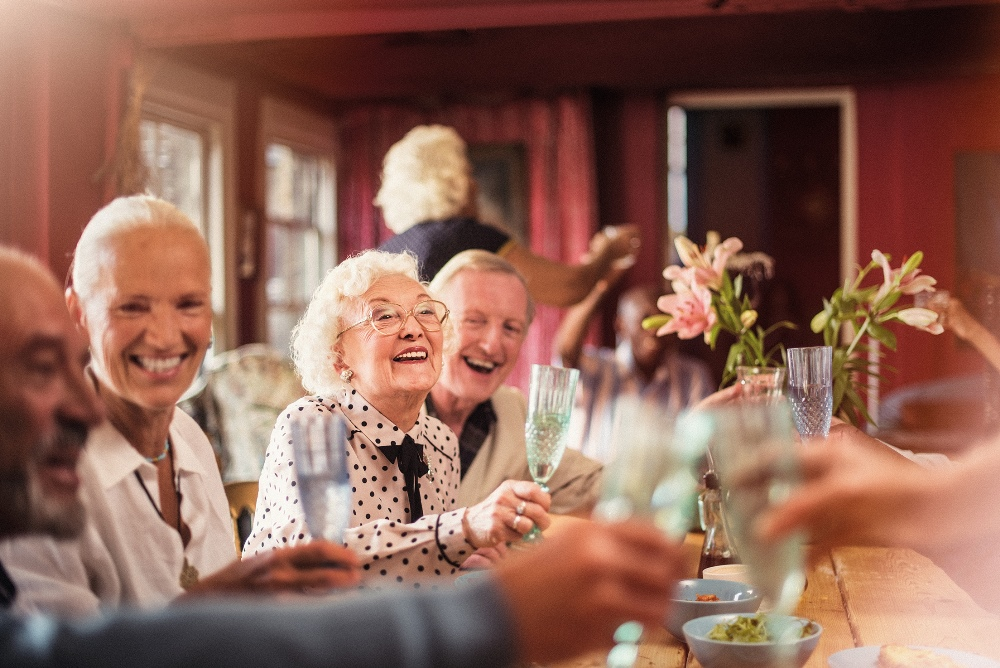 image of older people laughing together over a meal.