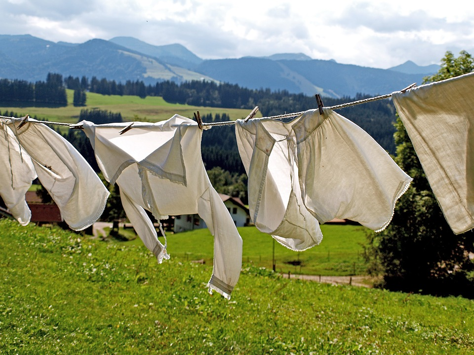 Four white clothing items hanging on a washing line.