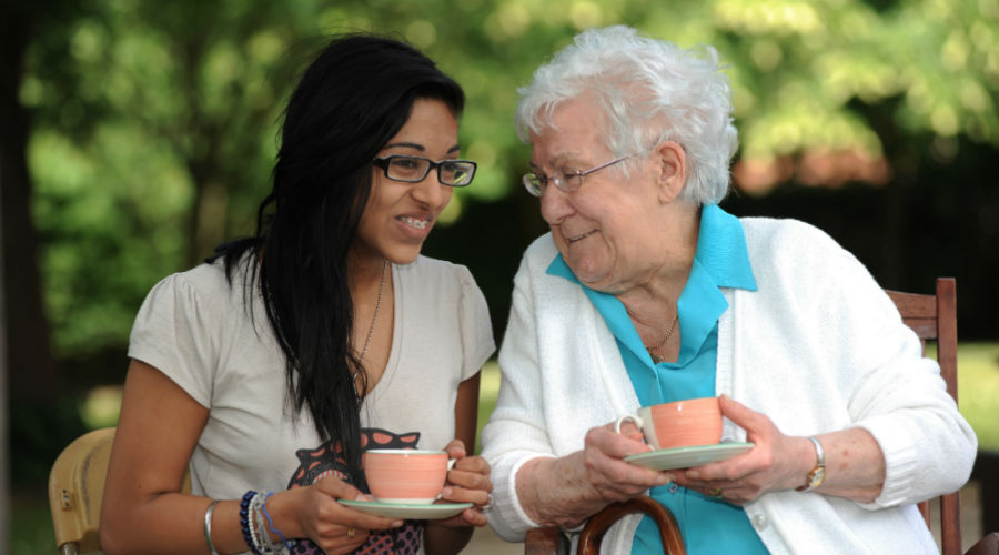 Elderly lady and young lady drinking tea