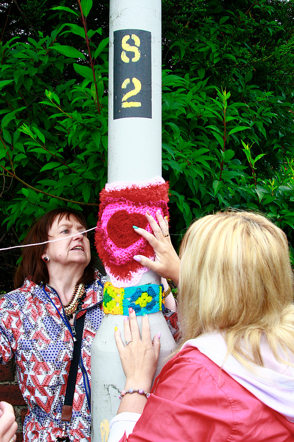 Two women sewing on knitted artwork to a tree.