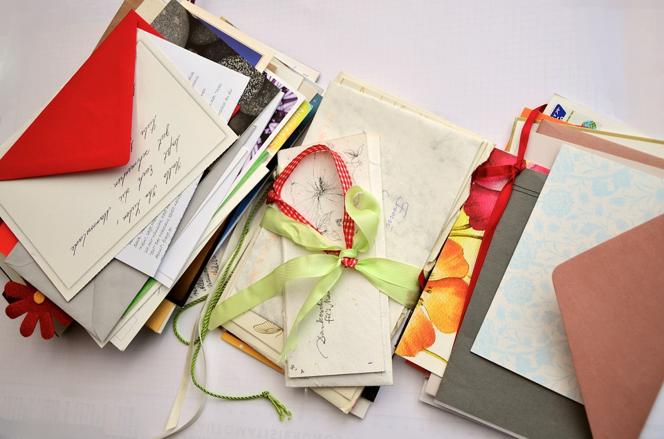 A pile of letters spread out, some with ribbon tied around them.
