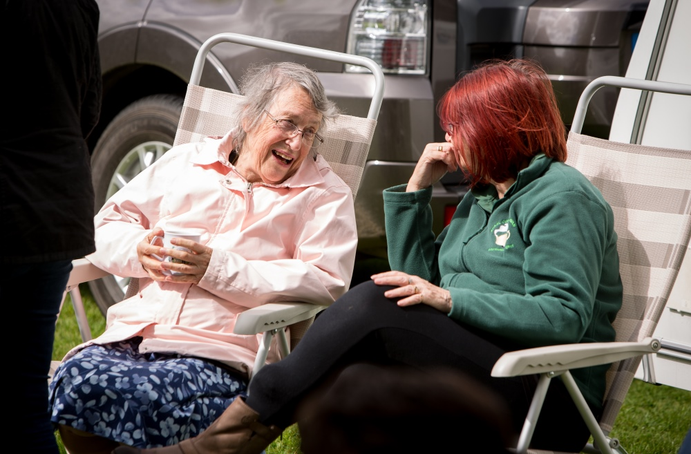An elderly woman speaking to another woman on chairs.