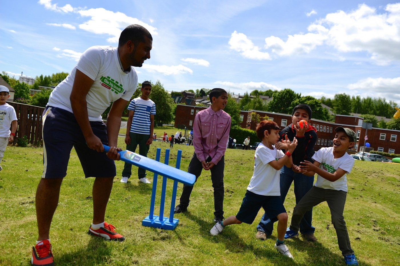 Photo of adults and children enjoying outdoor games in a community space