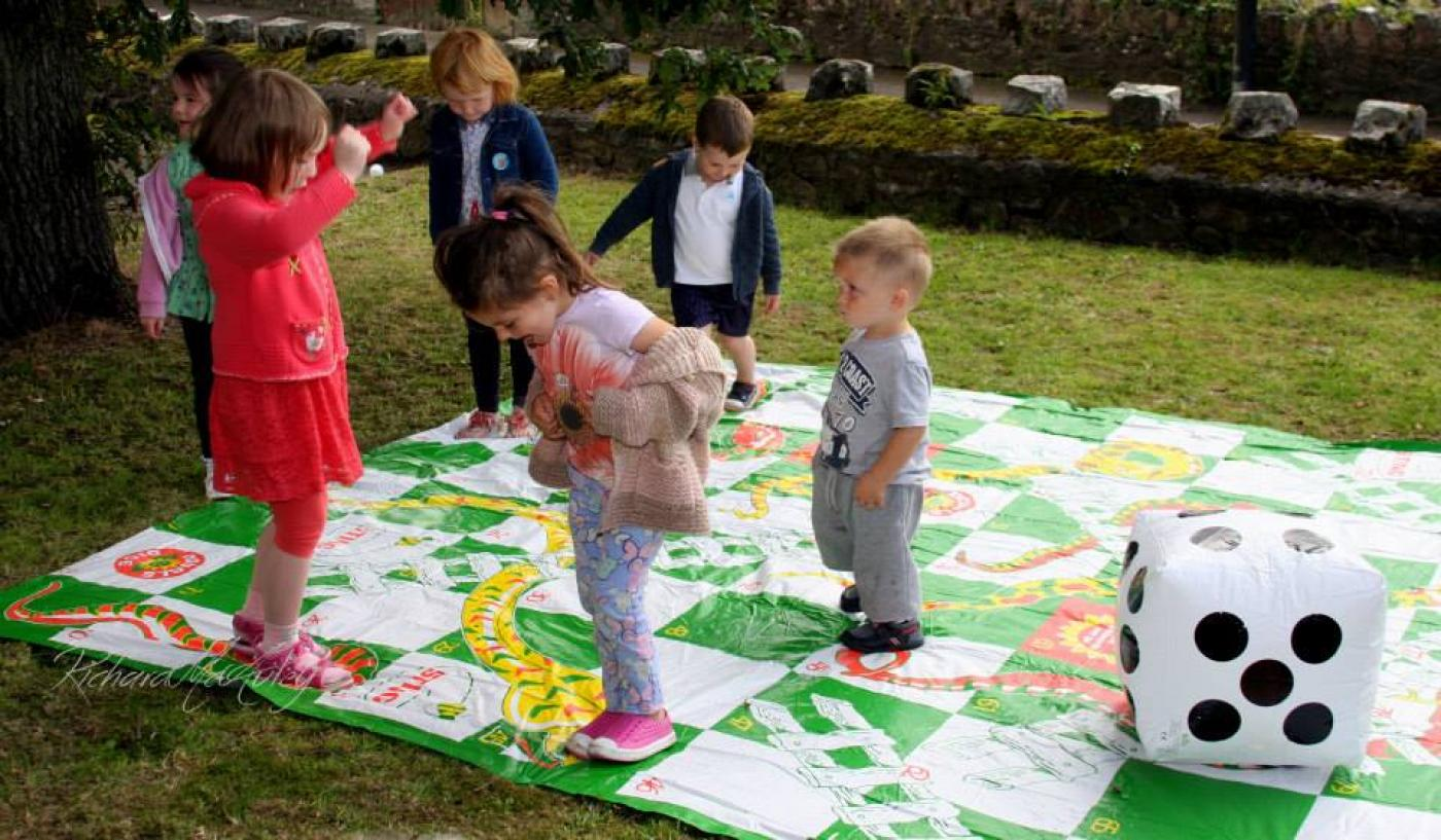 Children playing on a picnic blanket.