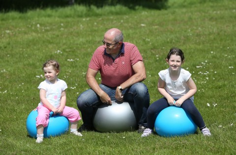 Photo of a man and children on space hoppers