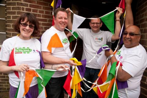 A group of people wearing The Big Lunch t-shirts holding brightly coloured bunting.