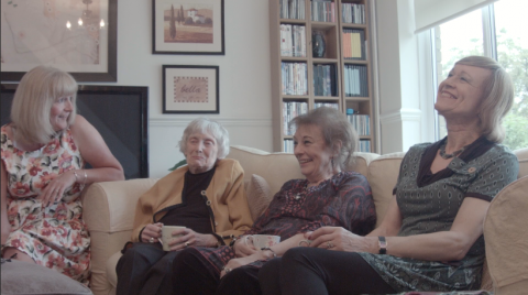 Four woman of varying ages talk on a couch.