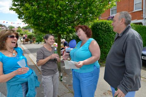 Four people chat and laugh on their street, one of the women is holding a list