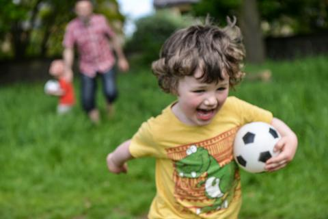 A young boys runs laughing with a ball in his hands