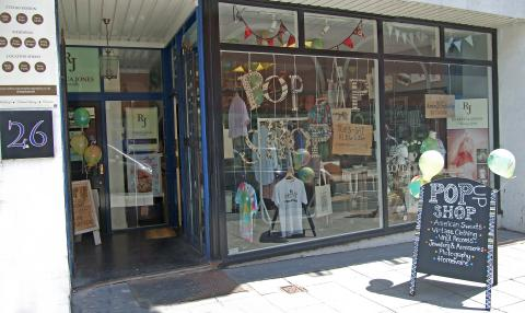 A pop up shop with clothing in the window.