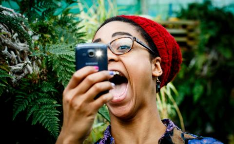 A woman taking a photograph with her phone.