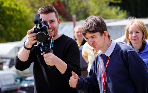 A man holding a video camera with a smiling man beside him.
