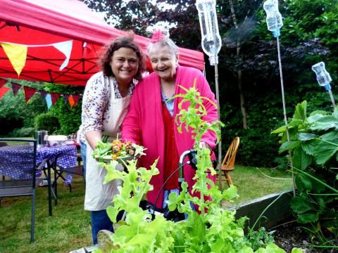 A woman and an elderly woman in a bright pink cardigan pose for a photo near a plant.