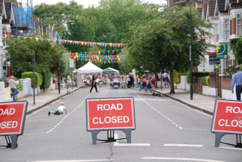 Three road closure signs with a street party in the distance and lots of bunting.