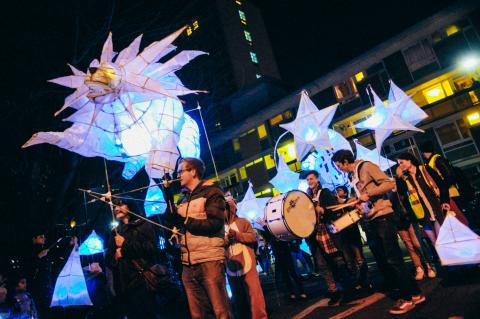 Men in a lantern parade with star lanterns.
