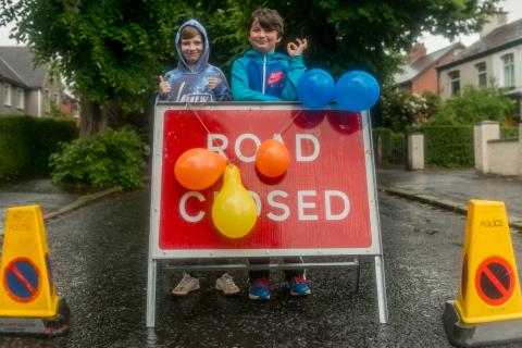 Two children standing in the rain behind a road closed sign that is covered in balloons.