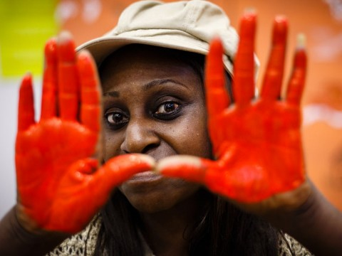 A woman peeking through paint stained hands.