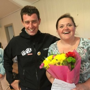 Photo of Team Scotland's Josh with Kathryn Davidson of Song Reivers at Tarset holding a bouquet of bright flowers.