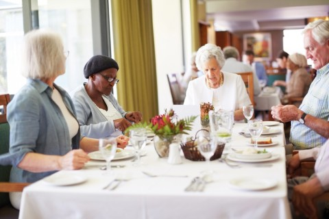 older people enjoying a meal at a table.