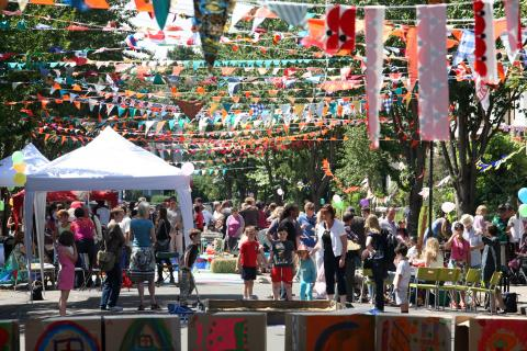 A busy street party decorated with bunting, Eden Project Communities