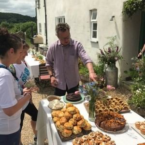 Photo of celebrity chef Hugh Fearnley-Whittingstall greeting Team Cornwall with a spread of food he made for the occasion.
