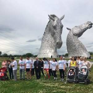 Photo of Team Scotland along with a group of people at Falkirk Wheel in front of a giant metal sculpture of two horse heads.