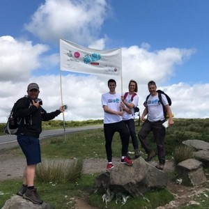 Photo of Team Wales holding up a Great Big Walk banner, whilst standing on rocks.