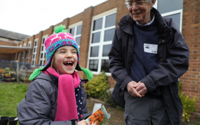 Child with packet of seeds laughing with an older gentleman who is helping her
