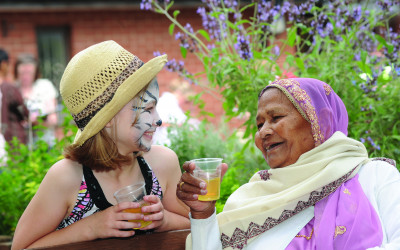A young girl with her face painted as a cat laughs with an older lady at The Big Lunch