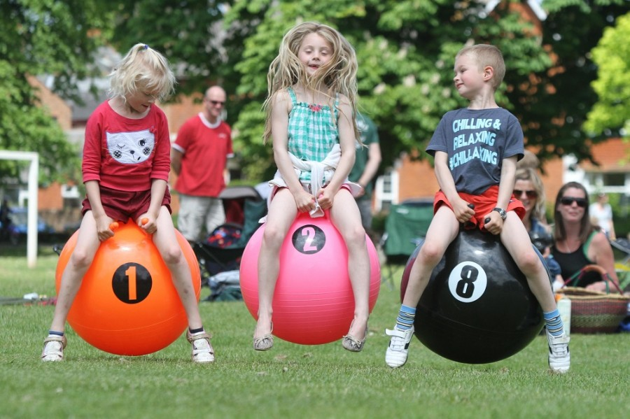 Photo of children playing on space hoppers outdoors