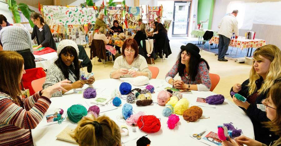 A group of women sit at a table with balls of wool.