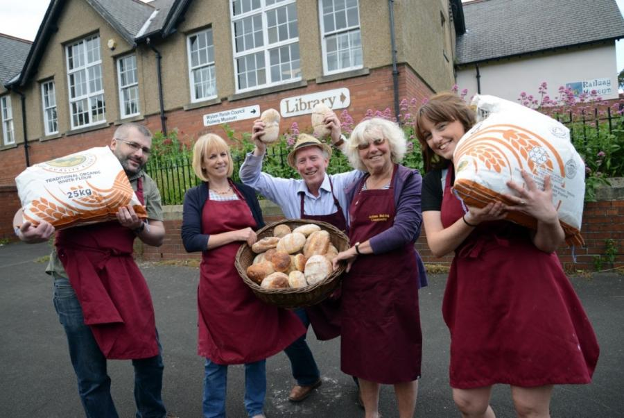 A group of people outside wearing aprons and carrying sacks of flour.