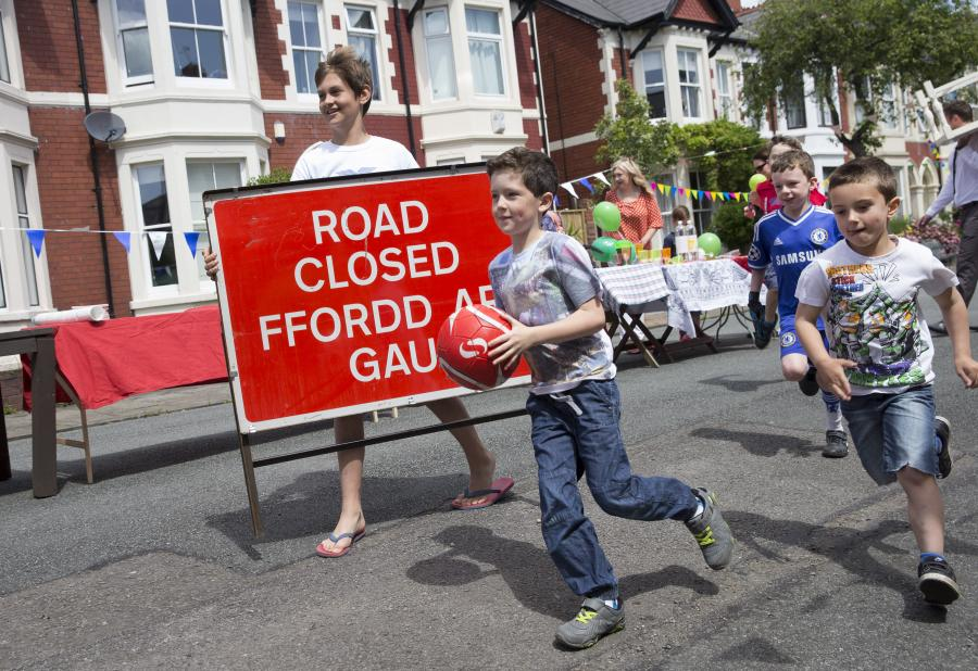 Children playing on the road with a road closure sign.