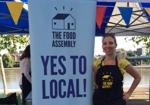 A woman wearing an apron standing in front of a Food Assembly stand.