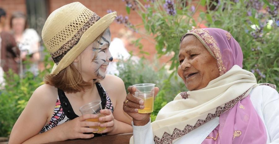 A young girl with her face painted sits smiling at an elderly woman.