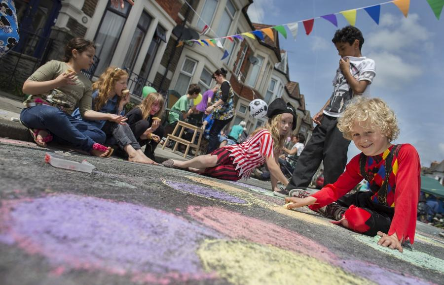A little boy drawing in chalk on the pavement.